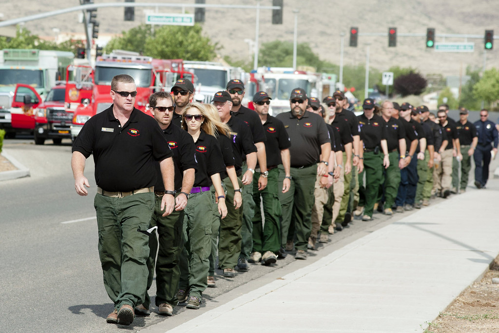 Description of . Members of the Southwest Area Incident Management Team walk to the memorial service honoring the 19 firefighters killed in a wildfire at Tim's Toyota Center July 9, 2013 in Prescott Valley, Arizona. (Photo by Laura Segall/Getty Images)