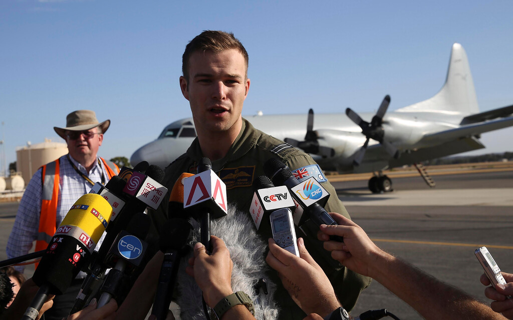 Description of . In this photo provided by China's Xinhua News Agency, Royal Australian Air Force (RAAF) Flight Lt. Russell Adams who piloted the P-3 Orion search and rescue aircraft speaks to the media after he returned from their search operation for the missing Malaysia Airlines flight MH370, at Pearce Airbase near Perth, Australia, Friday, March 21, 2014.  Search planes scoured a remote patch of the Indian Ocean but came back empty-handed Friday after a 10-hour mission looking for any sign of the missing Malaysia Airlines jet, another disappointing day in one of the world's biggest aviation mysteries. (AP Photo/Xinhua, Xu Yanyan)