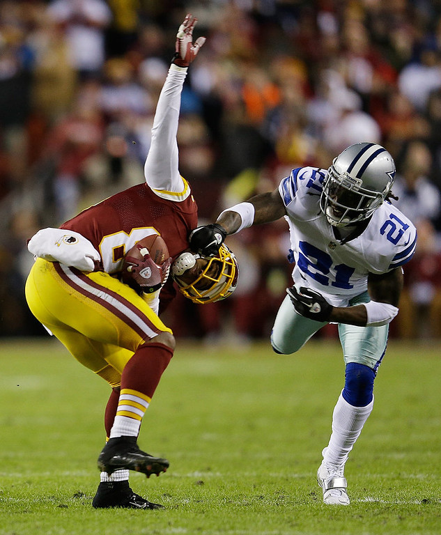 Description of . Santana Moss #89 of the Washington Redskins is tackled  by Mike Jenkins #21 of the Dallas Cowboys after catching a pass in the first quarter at FedExField on December 30, 2012 in Landover, Maryland.  (Photo by Rob Carr/Getty Images)