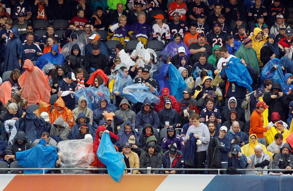 Description of . Fan start to put rain gear on as rain begins to fall at Soldier Field during the first half of an NFL football game between the Chicago Bears and Baltimore Ravens, Sunday, Nov. 17, 2013, in Chicago. (AP Photo/Kiichiro Sato)