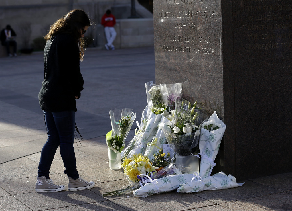 Description of . A woman reflects in front of a makeshift memorial honoring Boston University student Lingzi Lu, who was killed in the Boston Marathon explosions, Wednesday, April 17, 2013, in Boston. The city continues to cope following Monday's explosions near the finish line of the marathon, which claimed three lives. (AP Photo/Julio Cortez)
