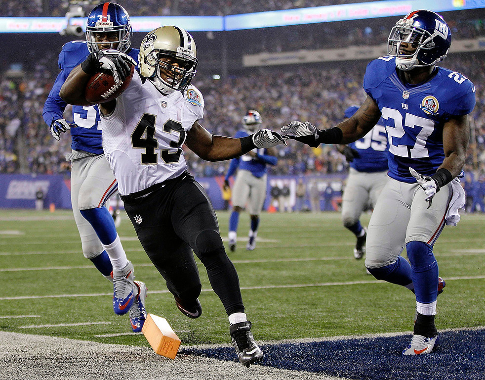 Description of . New Orleans Saints running back Darren Sproles (43) scores on a 9-yard touchdown run ahead of New York Giants defensive back Will Hill (31) and Stevie Brown (27) during the second half of an NFL football game, Sunday, Dec. 9, 2012, in East Rutherford, N.J. (AP Photo/Kathy Willens)