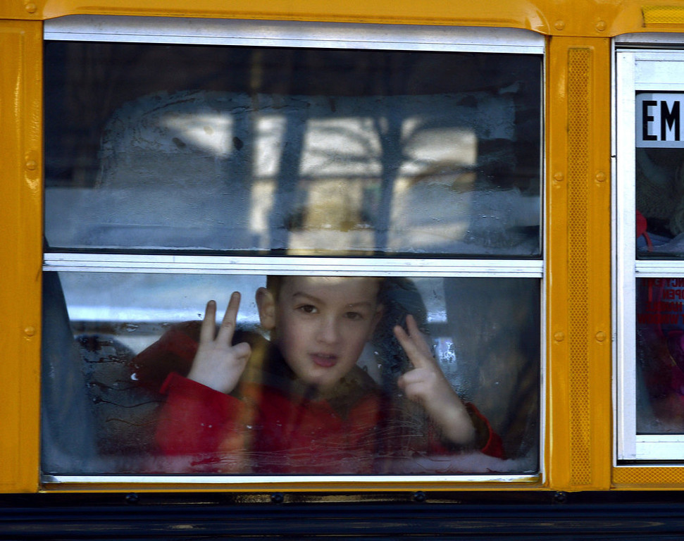 Description of . A Sandy Hook Elementary student flashes a sign as children leave on a school bus  in Newtown, Connecticut on January 3, 2013.  Students at the elementary school where a gunman massacred 26 children and teachers last month were returning Thursday to classes at an alternative campus described by police as