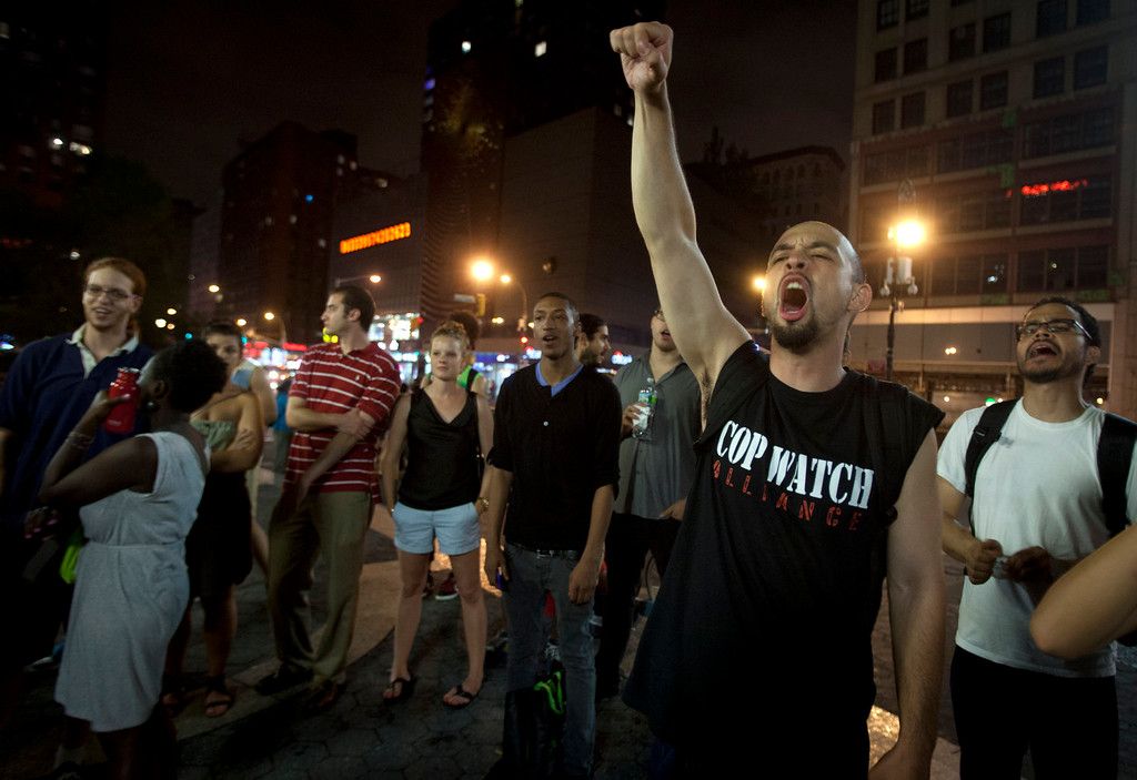 Description of . A man screams during a demonstration in Union Square after the news that George Zimmerman was found not guilty in the 2012 shooting death of teenager Trayvon Martin on Saturday, July 13, 2013 in New York. (AP Photo/Carlo Allegri)