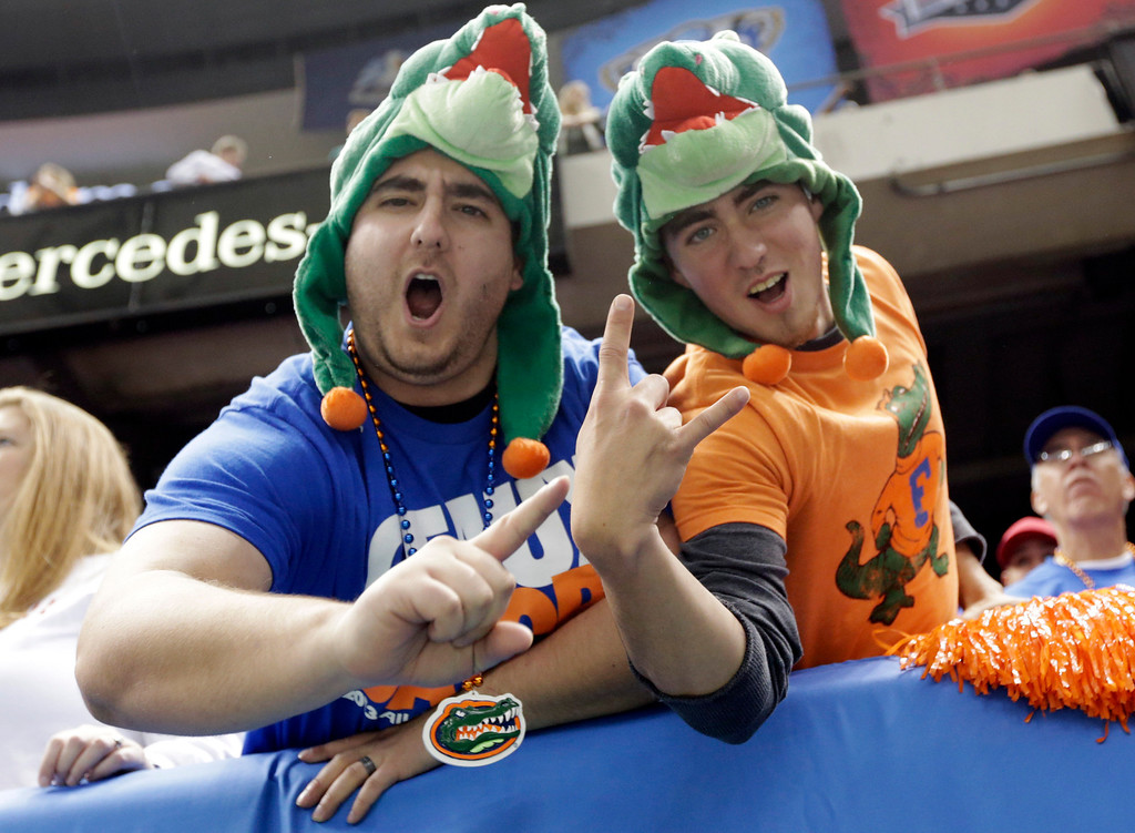Description of . Mark and Dustin Ware of Atlanta cheer for the Gators prior to the start of the Sugar Bowl NCAA college football game between Florida and Louisville on Wednesday, Jan. 2, 2013, in New Orleans. (AP Photo/Dave Martin)