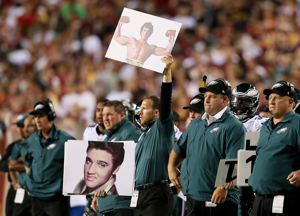 Description of . Philadelphia Eagles coaches hold up Rocky and Elvis signs in the second quarter while taking on the Washington Redskins at FedExField on September 9, 2013 in Landover, Maryland.  (Photo by Rob Carr/Getty Images)