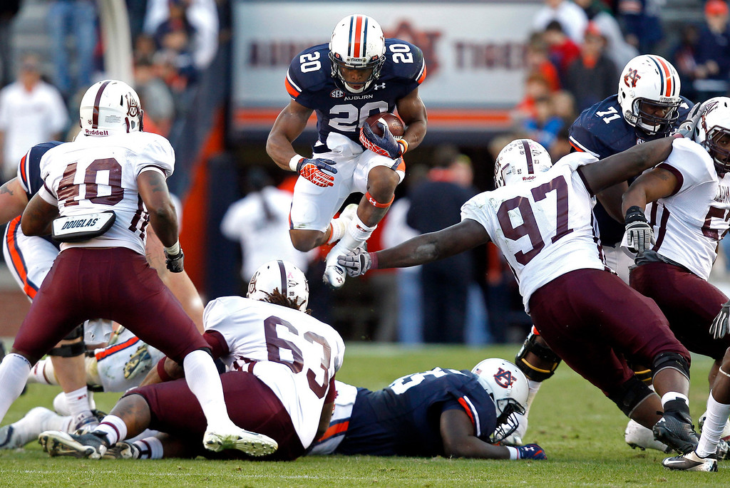 Description of . Auburn running back Corey Grant (20) jumps over the pile for extra yardage during the second half of an NCAA college football game against ALabama A&M on Saturday, Nov. 17, 2012 in Auburn, Ala. Auburn defeated Alabama A&M 51-7. (AP Photo/Butch Dill)