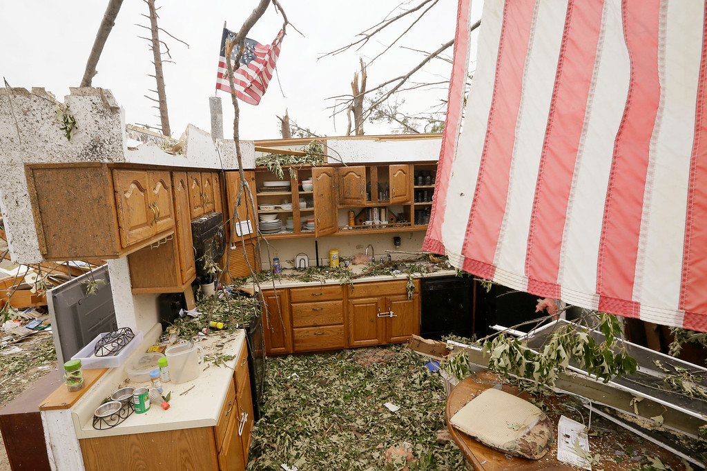 Description of . Flags fly over two walls that remain of a house in Mayflower, Ark., Tuesday, April 29, 2014.  On Sunday evening, roughly 15 tornadoes carved a path of destruction in the South and the country's midsection, according to estimates from the National Oceanic and Atmospheric Administration's Storm Prediction Center. On Monday, around 50 tornadoes ravaged the South, the agency said.  (AP Photo/Danny Johnston)