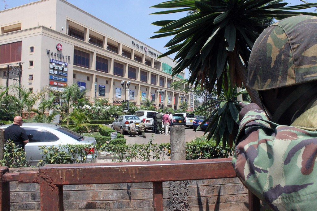 Description of . A soldier aims his weapon outside the Westgate Mall, an upscale shopping mall  in Nairobi, Kenya Saturday Sept. 21 2013, where shooting erupted when armed men staged an attack.   (AP Photo/Jason Straziuso)