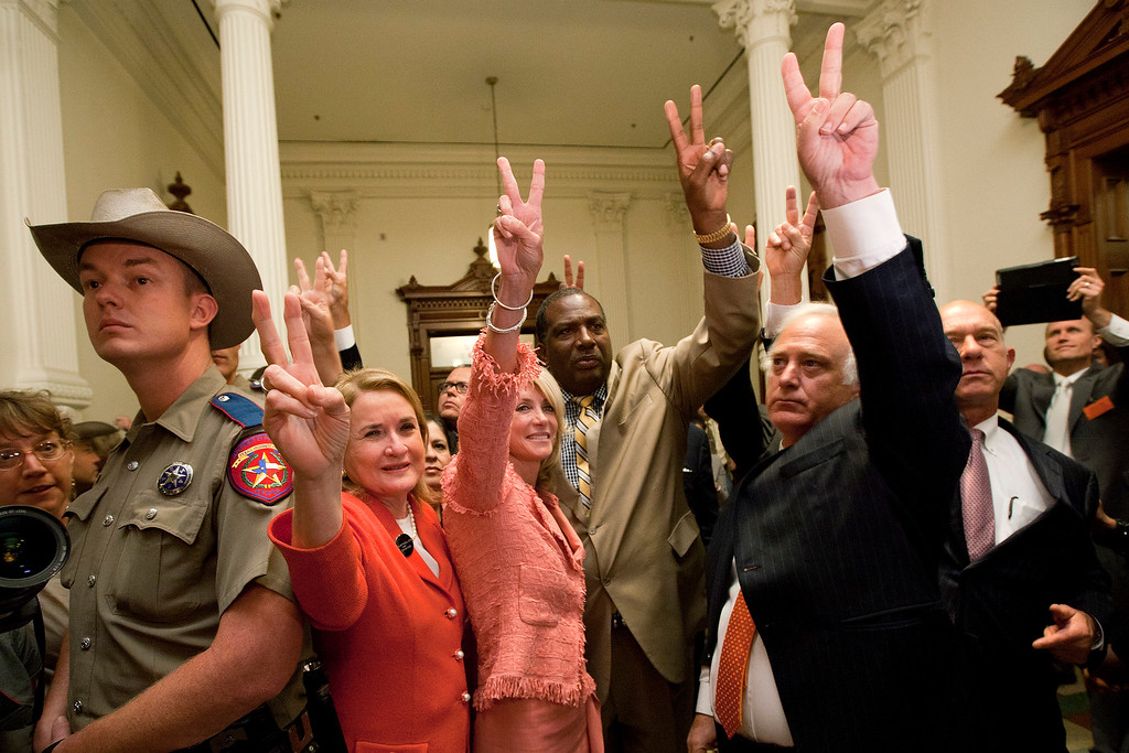 Description of . State Senators, from third from left,  Sylvia R. Garcia, D-Houston, Wendy Davis, D-Fort Worth, Royce West, D-Dallas, Kirk Watson, D-Austin and John Whitmire, D-Houston,  greet abortion rights advocates to show they voted against HB2, which the Senate approved late Friday night, July 12, 2013.  Republicans in the Texas Legislature passed an omnibus abortion bill that is one of the most restrictive in the nation, but Democrats vowed Saturday to fight both in the courts and the ballot box as they used the measure to rally their supporters. (AP Photo/Tamir Kalifa)