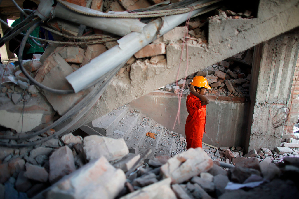 Description of . A rescue worker stands among the rubble as he takes part in the rescue process after the Rana Plaza building collapsed, in Savar, 30 km (19 miles) outside Dhaka April 24, 2013. REUTERS/Andrew Biraj