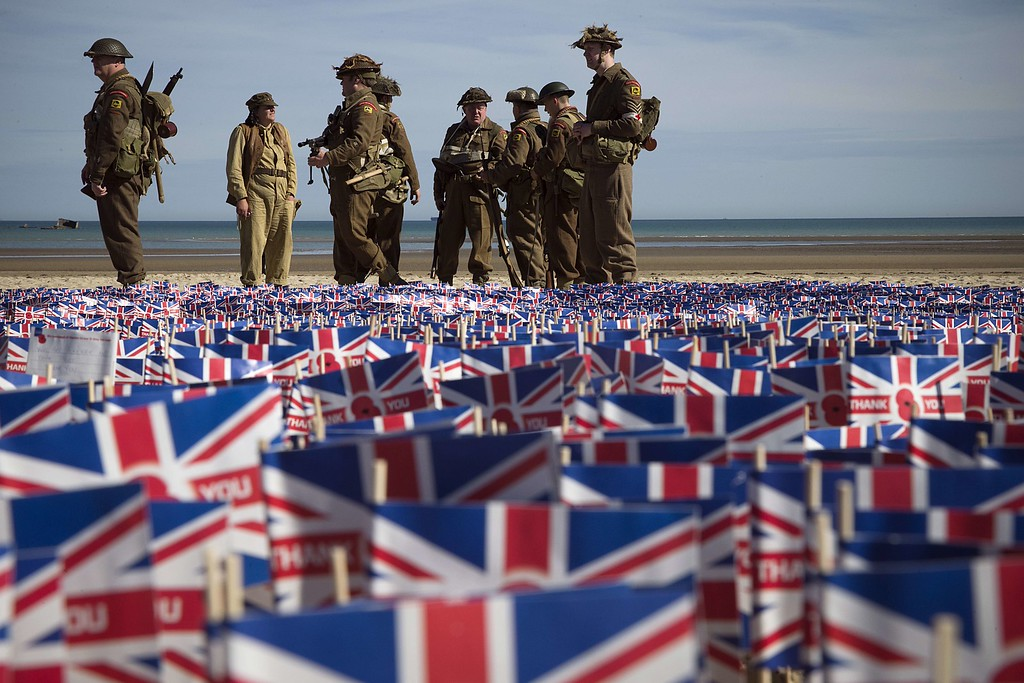 Description of . People wearing WWII British uniforms stand in front of British national flags on June 6, 2014 in Asnelles, Normandy, during a ceremony on the