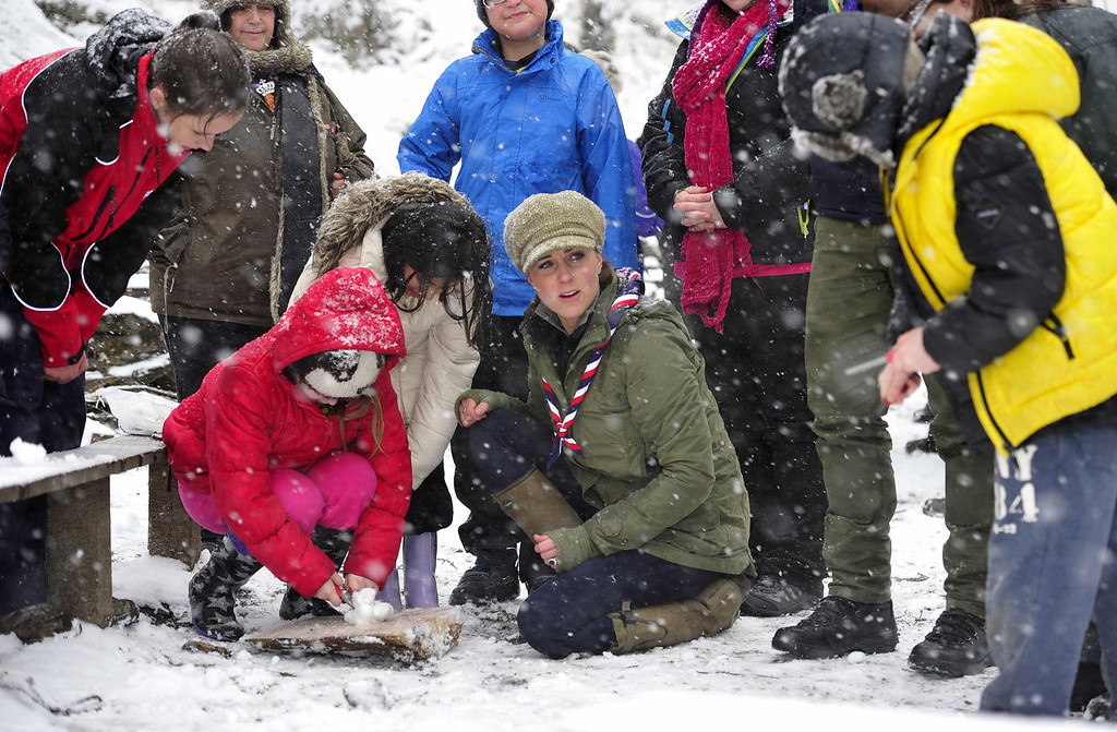 Description of . Catherine, Duchess of Cambridge (C) offers assistance in firelighting during a visit to the Great Tower Scout camp at Newby Bridge in Cumbria on March 22, 2013.   The Duchess braved snowy conditions to pay a visit to the scout camp.  ANDY STENNING/AFP/Getty Images