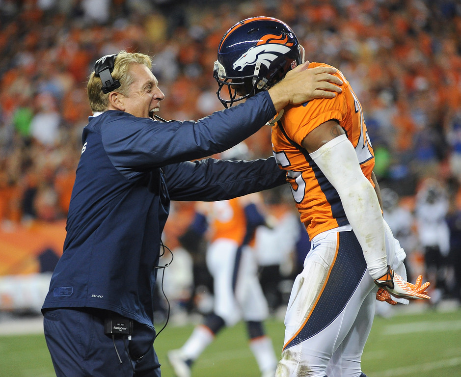 Description of . Defensive coach Jack Del Rio celebrates Denver Broncos cornerback Chris Harris's (25) interception in the second quarter. (Photo by Tim Rasmussen/The Denver Post)