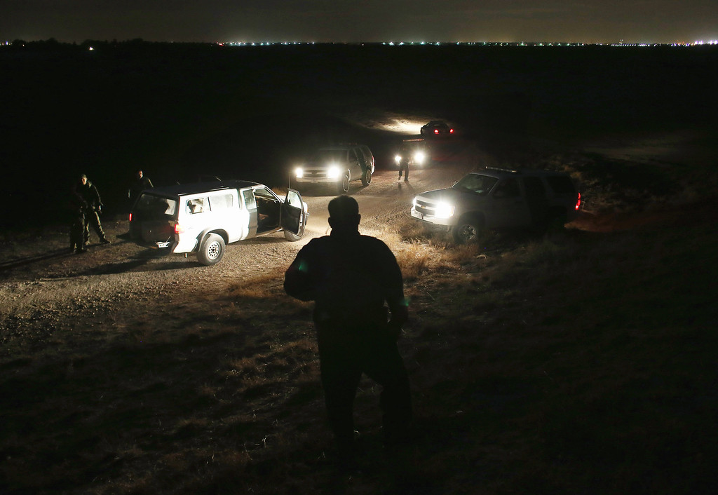 Description of . MCALLEN, TX - APRIL 10:  U.S. Border Patrol agents inspect a pickup load (L), of marijuana seized from drug smugglers near the U.S.-Mexico border on April 10, 2013 in Hidalgo, Texas. The agents, guided by helicopter surveillance from the U.S. Office of Air and Marine, waited more than four hours in hiding before seizing more than 900 pounds of the drug. The smugglers ran and escaped by swimming back across the Rio Grande River into Mexico. Border Patrol agents say they have also seen an additional surge in immigrant traffic since immigration reform negotiations began this year in Washington D.C. Proposed refoms could provide a path to citizenship for many of the estimated 11 million undocumented workers living in the United States.  (Photo by John Moore/Getty Images)