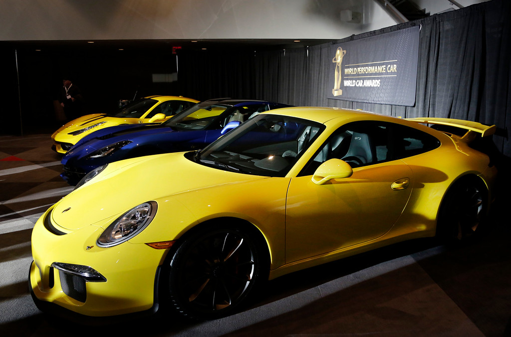 Description of . The 2015 Porsche 911 GT3, front, wins the World Car of the Year Award in the Performance Car category at the New York International Auto Show, Thursday, April 17, 2014 in New York. (AP Photo/Mark Lennihan)