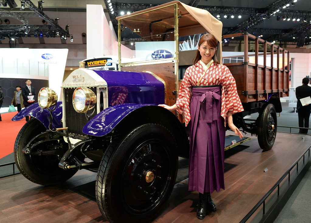 Description of . A model stands beside a 1924 Wolseley CP 1.5-ton truck at the Isuzu booth during the Tokyo Motor Show in Tokyo on November 20, 2013.          AFP PHOTO / TOSHIFUMI KITAMURA/AFP/Getty Images
