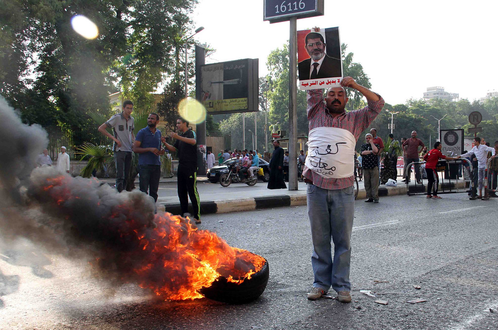 Description of . A supporter of Egypt's Muslim Brotherhood holds a picture of ousted Egyptian president Mohamed Morsi as he stands next to burning tyres while wearing a piece of white cloth reading