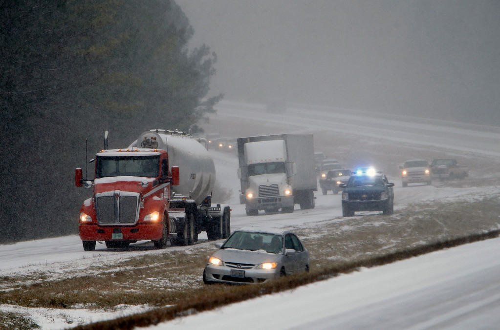 Description of . Vehicles are backed up on a snow covered US Highway 280 during a snow storm, Tuesday, Jan. 28,  2014 in Chelsea, Ala. A fast-moving, unexpectedly severe winter storm blanketed much of Alabama with a treacherous layer of frozen precipitation Tuesday, causing multiple wrecks, stranding hundreds of children in schools and coating palm trees with ice at the beach.  (AP Photo/Hal Yeager)