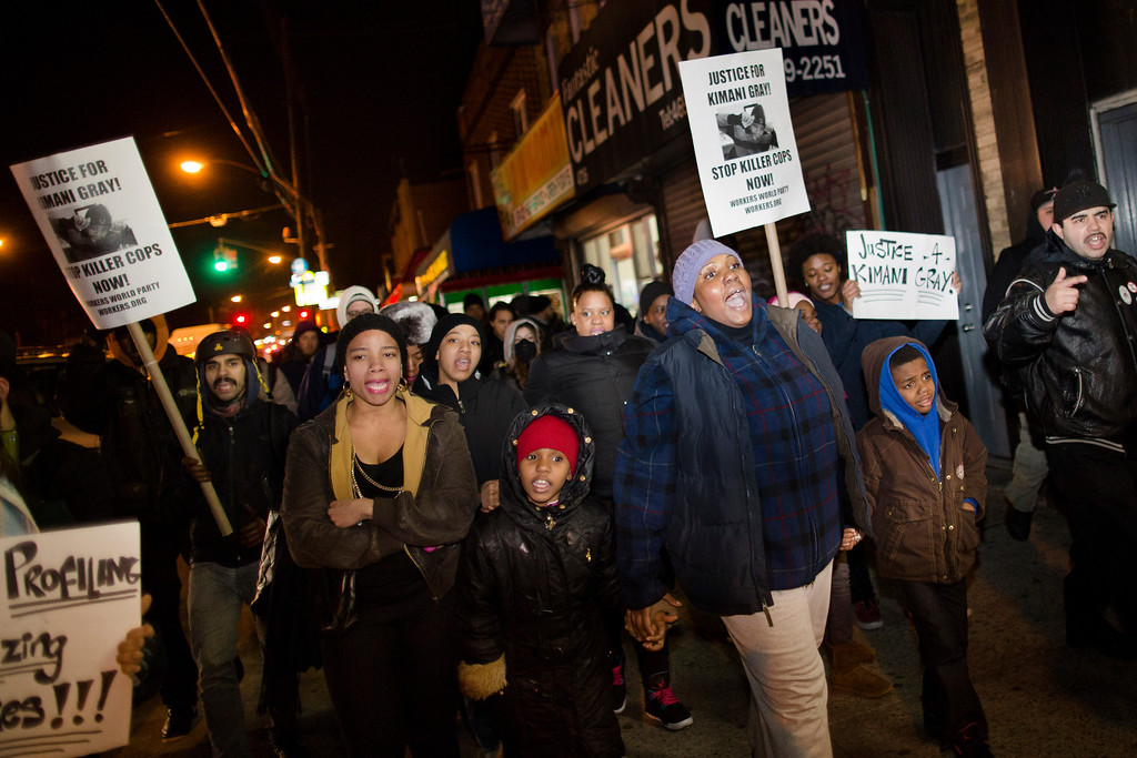 Description of . Demonstrators march through East Flatbush as they protest against the shooting of Kimani