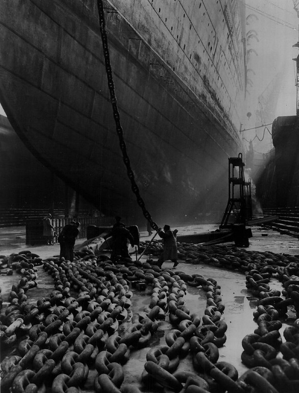 Description of . The massive anchor chains of the Queen Elizabeth are spread out in a Southampton dry dock as the giant liner receives her annual cleanup on Jan. 25, 1953. This year, she will carry thousands of passengers across the Atlantic to see the June 2 coronation. (British Information Services)
