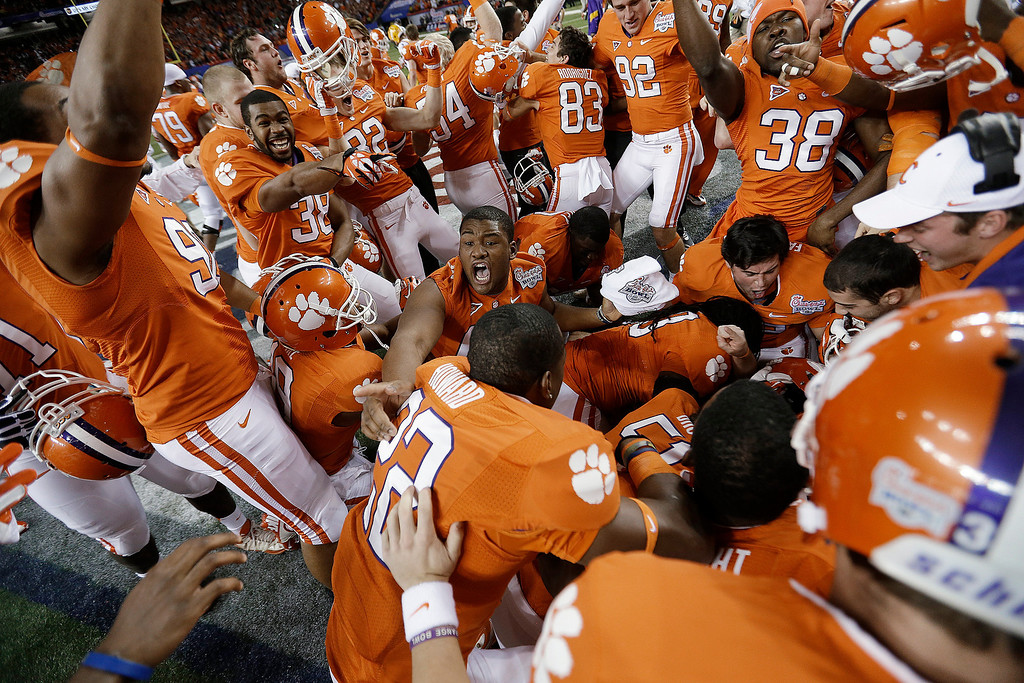 Description of . Clemson players pile up in the middle of the field after the Chick-fil-A Bowl NCAA college football game against LSU, Monday, Dec. 31, 2012, in Atlanta. Clemson won 25-24 on a field goal as time expired. (AP Photo/David Goldman)