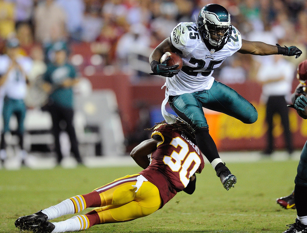 Description of . Philadelphia Eagles running back LeSean McCoy (25) leaps over Washington Redskins cornerback E.J. Biggers as he breaks free for a touchdown run during the second half of an NFL football game in Landover, Md., Monday, Sept. 9, 2013. (AP Photo/Nick Wass)
