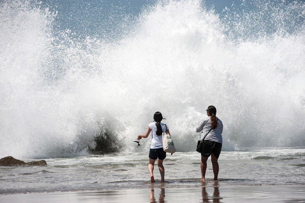 Description of . Cece, left, and Jennifer, of Orange County, run as big waves crash the shoreline, Tuesday, Aug. 26, 2014, at Venice Beach, Calif. (AP Photo/The Orange County Register, Ed Crisostomo)