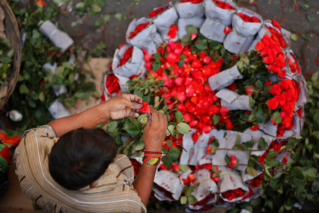 Description of . A man prepares to make rose bouquets to sell on the occasion of Christmas at a wholesale market in Mumbai, India, Wednesday, Dec. 25, 2013. Although Christians comprise only two percent of the population among a Hindu majority, the holiday is observed across the country as an occasion to celebrate. (AP Photo/Rajesh Kumar Singh)