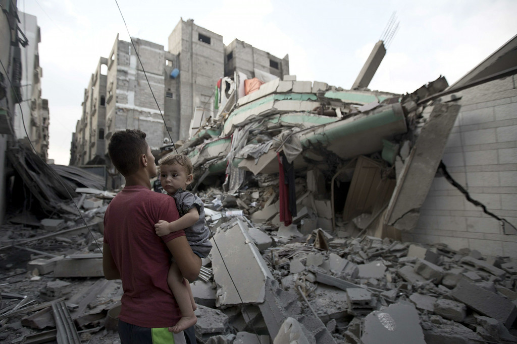 Description of . A Palestinian man carrying a child looks at the destroyed house of Hamas top leader in Gaza, Ismail Haniya, after it was hit by an overnight Israeli air strike, on July 29, 2014 in Gaza City. Bloodshed in and around Gaza surged with strikes killing at least 13 Palestinians, a day after five Israeli soldiers died, shattering hopes for an end to three weeks of violence. AFP PHOTO/MAHMUD  HAMS/AFP/Getty Images