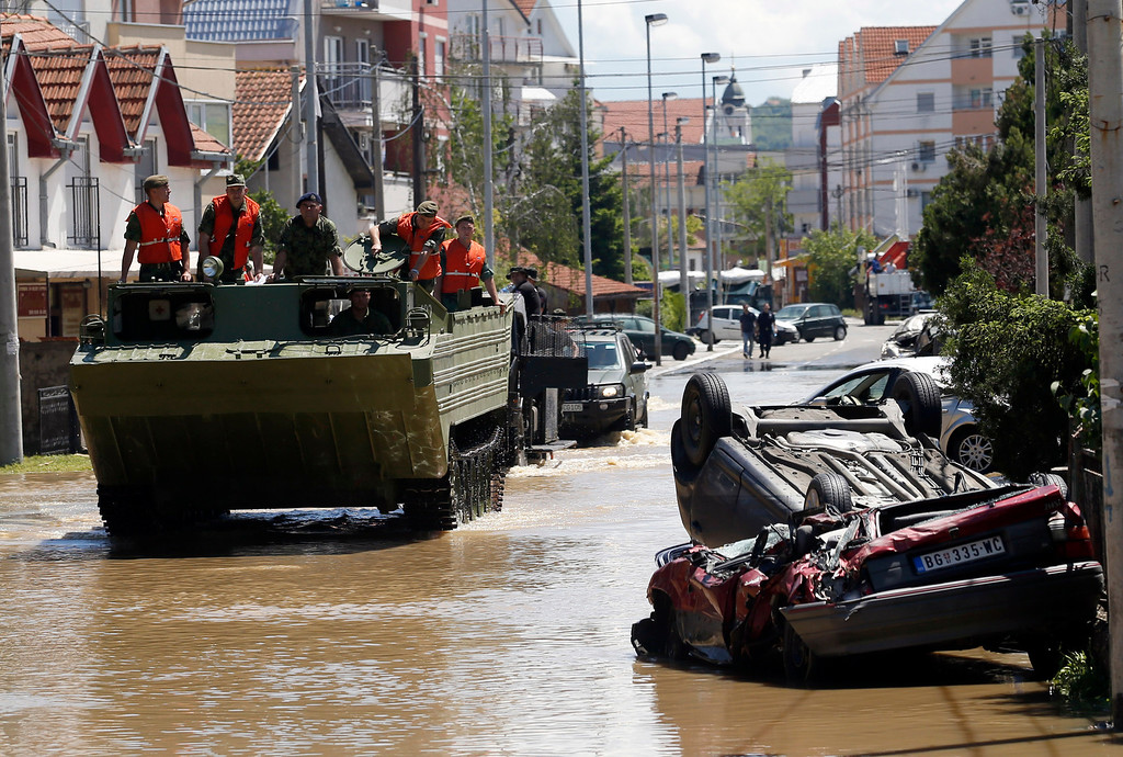 Description of . A military amphibious vehicle drives through street where flood waters are retreating in Obrenovac, some 30 kilometers (18 miles) southwest of Belgrade, Serbia, Monday, May 19, 2014. Belgrade braced for a river surge Monday that threatened to inundate Serbia's main power plant and cause major power cuts in the crisis-stricken country as the Balkans struggle with the consequences of the worst flooding in southeastern Europe in more than a century. At least 35 people have died in Serbia and Bosnia in the five days of flooding caused by unprecedented torrential rain, laying waste to entire towns and villages and sending tens of thousands of people out of their homes, authorities said. (AP Photo/Darko Vojinovic)
