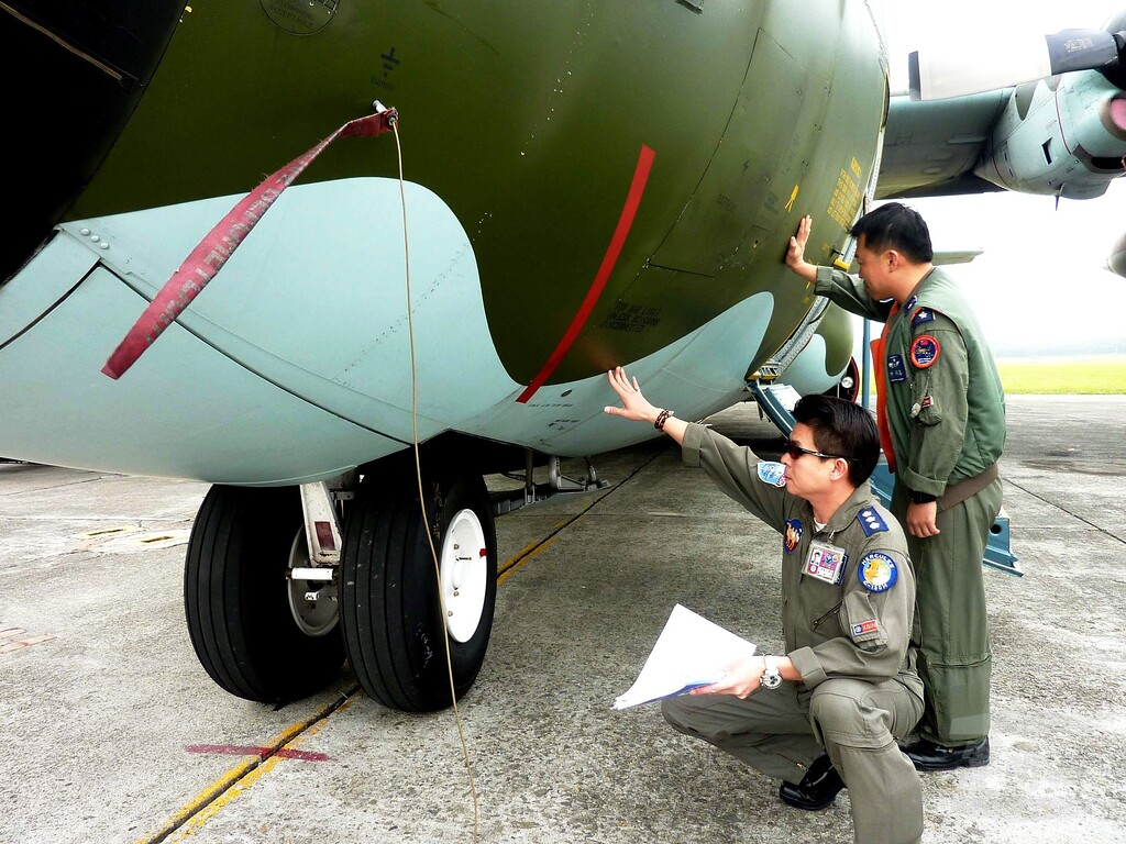 Description of . A handout picture provided by the Military News Agency shows Taiwan Air Force personnel checking a C-130 military transport plane before it took off at Pingtung Air Base in Pingtung, southern Taiwan, on 12 March 2014, to join in the search for the missing Malaysia Airlines plane over the South China Sea.  EPA/MILITARY NEWS AGENCY HANDOUT