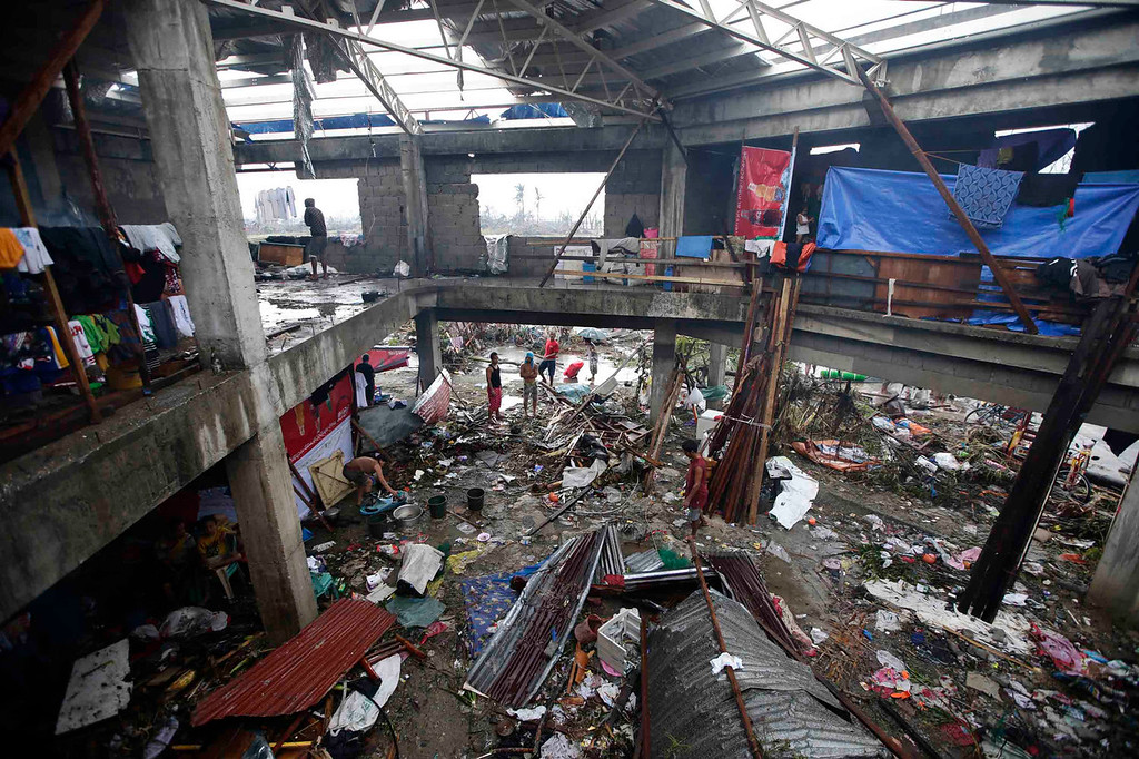 Description of . Residents stand outside damaged structures in Tacloban city, Leyte province central Philippines on Sunday, Nov. 10, 2013. The city remains littered with debris from damaged homes as many complain of shortage of food, water and no electricity since the Typhoon Haiyan slammed into their province. Haiyan, one of the strongest storms on record, slammed into six central Philippine provinces Friday leaving a wide swath of destruction and hundreds of people dead. (AP Photo/Bullit Marquez)