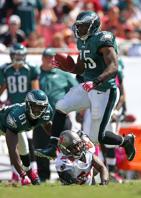 Description of . LeSean McCoy #25 of the Philadelphia Eagles jumps over Darrelle Revis #24 of the Tampa Bay Buccaneers during a game  at Raymond James Stadium on October 13, 2013 in Tampa, Florida.  (Photo by Mike Ehrmann/Getty Images)