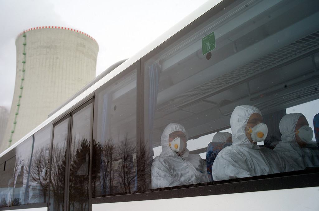 Description of . Workers of Dukovany nuclear power plant dressed in radiation protection suits sit in the bus during a nuclear accident exercise on March 26, 2013 in Dukovany nuclear power plant, 50km from the city of Brno. MICHAL CIZEK/AFP/Getty Images