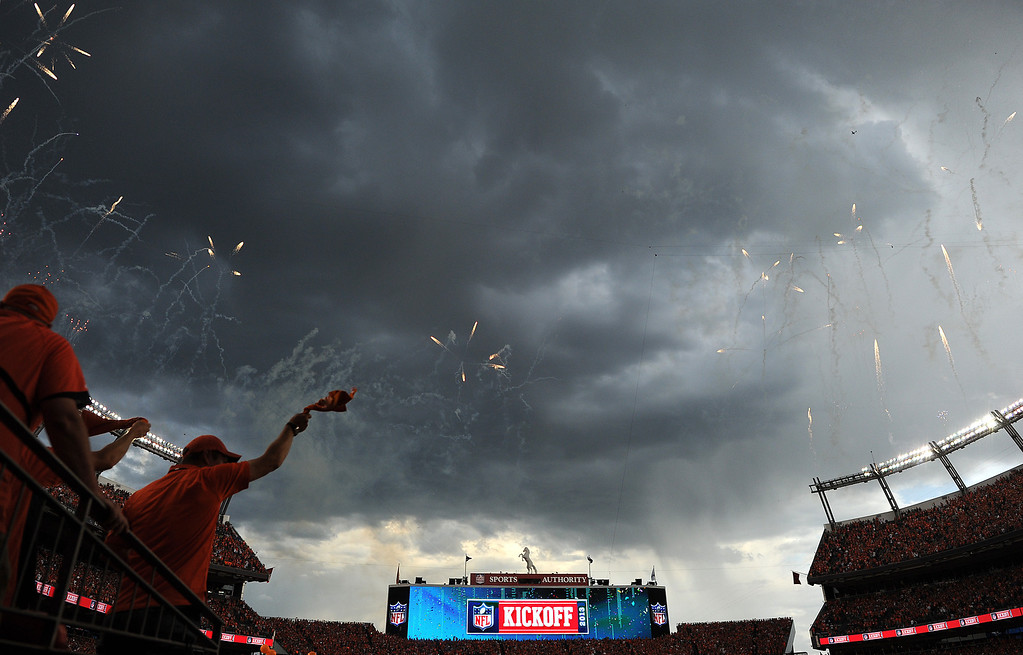 Description of . A storm moves in over the stadium as fireworks go off and balloons are released into the sky before the start of the game. Lighting in the area postponed the start of the game(Photo by Joe Amon/The Denver Post)