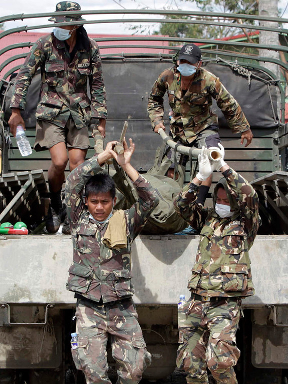 Description of . Soldiers unload a body bag, containing the body of their comrade who drowned during flashfloods at the height of Typhoon Bopha, from an army truck in New Bataan town in Compostela Valley, southern Philippines December 8, 2012.  Philippine President Benigno Aquino declared a state of national calamity on Saturday, four days after this year's strongest typhoon left nearly 1,000 people dead or missing mostly in the country's resource-rich south. REUTERS/Erik De Castro