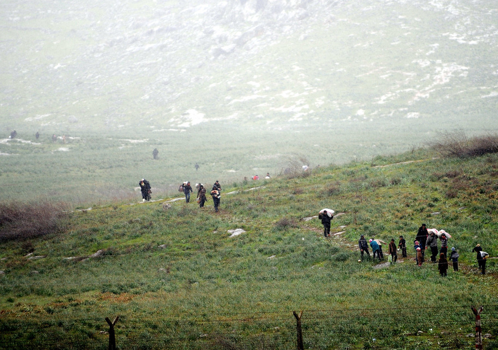 Description of . Syrian refugees walk across a feild on the Syrian side of the border before crossing into Turkey at Reyhanli in Antakya, on March 14, 2012. International mediator Kofi Annan called for an immediate halt to the killing of civilians in Syria as he arrived in Turkey for talks on the crisis. Activists said that the Syrian army launched a new assault in the restive northern province of Idlib and the city itself, where residents are suffering