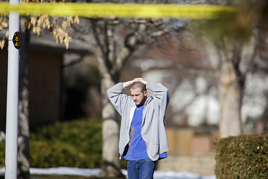 Description of . A neighbor takes in the scene at a town home where four people were killed Saturday morning including the gunman who held police at bay for several hours at the complex January 5, 2013 in Aurora, Colorado. Aurora SWAT team members shot a gunman after he went to a second-floor window and fired at police. The gunman also allegedly fatally shot two men and a woman that he had taken hostage. One woman managed to escape from an upstairs back window, ran from the home and called police just before 3 a.m., said Cassidee Carlson, Aurora police spokeswoman.  (Photo by Marc Piscotty/Getty Images)