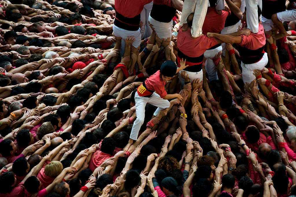 Description of . A young member of the Colla 'Vella de Valls' descends after bulding a human tower during the 24th Tarragona Castells Comptetion on October 7, 2012 in Tarragona, Spain. The 'Castellers' who build the human towers with precise techniques compete in groups, known as 'colles', at local festivals with aim to build the highest and most complex human tower. The Catalan tradition is believed to have originated from human towers built at the end of the 18th century by dance groups and is part of the Catalan culture.  (Photo by David Ramos/Getty Images)
