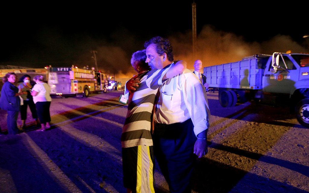 Description of . New Jersey Gov. Chris Christie, right, is hugged by Michael Cisneros, 14, during a visit to the area hit by a massive fire on the Seaside Park boardwalk, Thursday, Sept. 12, 2013, in Seaside Park, N.J. The fire apparently started in an ice cream shop and spread several blocks down the boardwalk to neighboring Seaside Heights. (AP Photo/Julio Cortez)