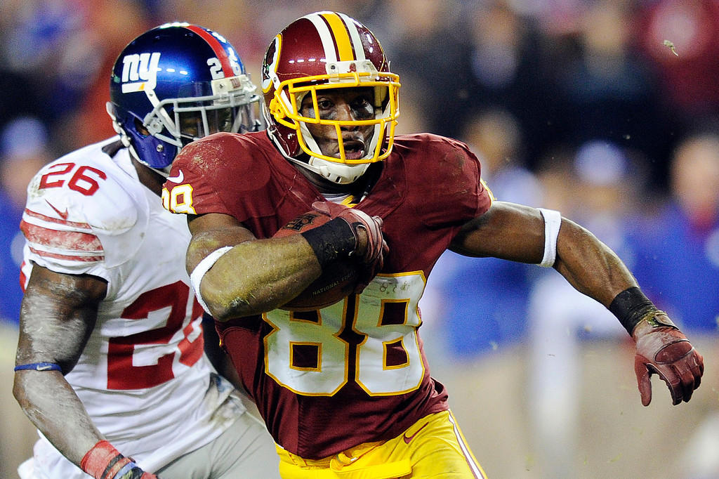 Description of . Washington Redskins wide receiver Pierre Garcon (88) carries the ball as New York Giants\' Antrel Rolle gives chase during the first half of an NFL football game in Landover, Md., Monday, Dec. 3, 2012. (AP Photo/Nick Wass)