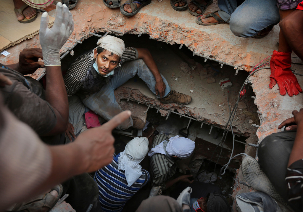 Description of . A Bangladeshi rescuer looks out from a hole cut in the concrete as he looks for survivors at the site of a building that collapsed Wednesday in Savar, near Dhaka, Bangladesh, Thursday, April 25, 2013. (AP Photo/Kevin Frayer)