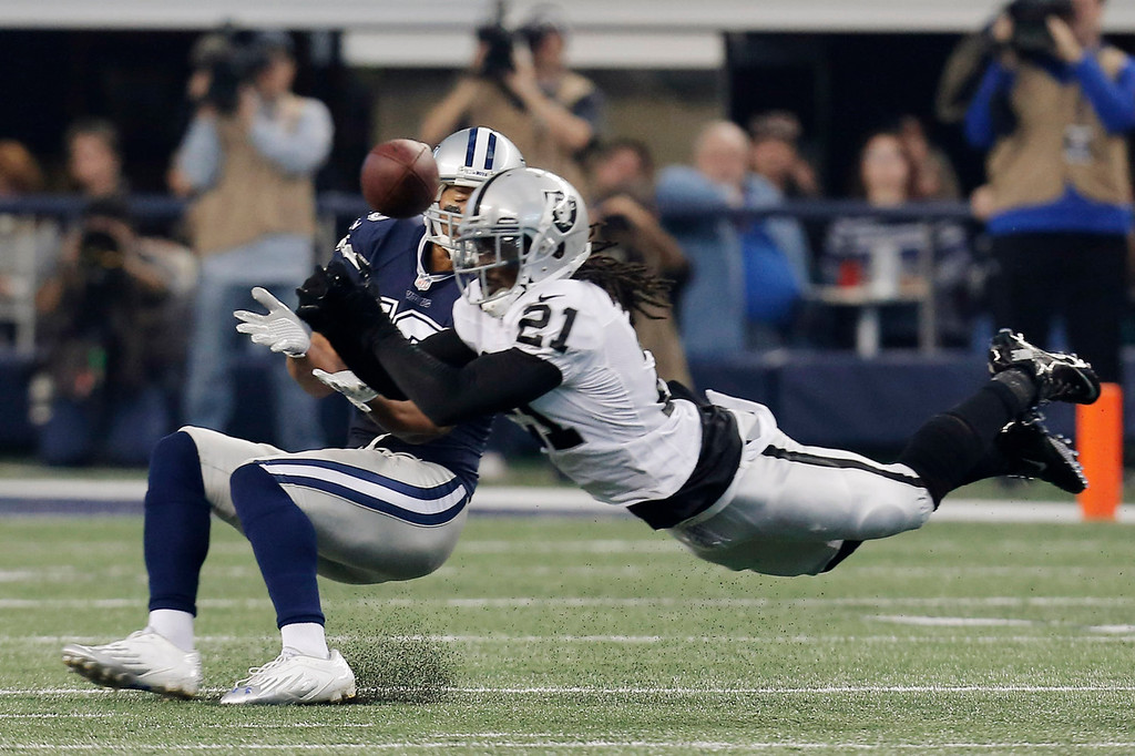 Description of . Oakland Raiders cornerback Mike Jenkins (21) breaks up a pass to Dallas Cowboys wide receiver Miles Austin (19) during the first half of an NFL football game, Thursday, Nov. 28, 2013, in Arlington, Texas.  (AP Photo/Brandon Wade)