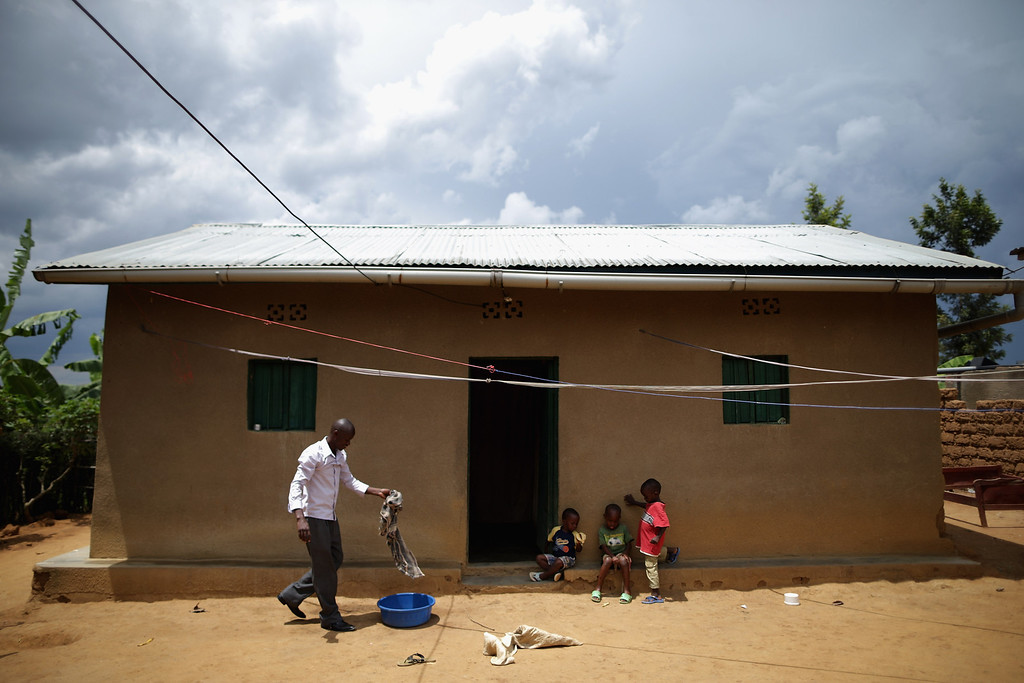 """. Silas Usengumuremyi cleans his home in a genocide \""""reconciliation village\"""" April 6, 2014 in Mybo, Rwanda. Silas was surprised several years ago when his next door neighbor, a Hutu man who participated in the 1994 genocide, offered to pay for a casket for Silas\' father, who was killed during the genocide. Organized by the Prison Fellowship Rwanda in 2004, this village of 285 is where those who served time in prison for genocide now live side-by-side with people who survived the killer\'s 1994 rampage. One of five communities like this in Rwanda, Mbyo residents share agriculture and handicraft cooperatives and say that working together has helped with reconciliation, easing their apprehension and fostering new friendships. Rwanda is preparing to commemorate the 20th anniversary of the country\'s 1994 genocide, when more than 800,000 ethnic Tutsi and moderate Hutus were slaughtered over a 100 day period.  (Photo by Chip Somodevilla/Getty Images)"""