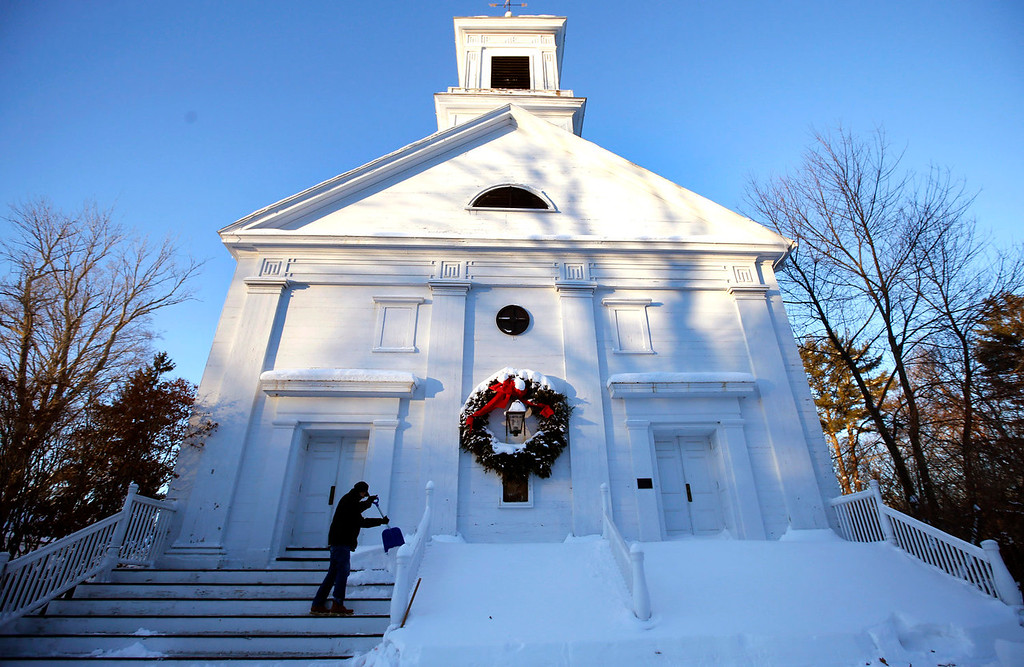 Description of . Fran Roche clears snow from the steps of First Church Congregational in Boxford, Mass. Friday, Jan. 3, 2014, in the wake of a winter storm which dumped up to 2 feet of snow there and in other areas north of Boston. (AP Photo/Elise Amendola) Massachusetts