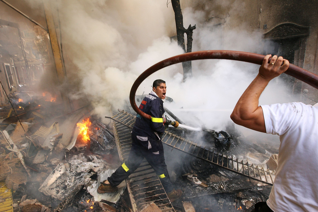 Description of . Firefighters extinguish fire at the scene of an explosion in Ashrafieh, central Beirut October 19, 2012. A huge car bomb exploded in a street in central Beirut during rush hour on Friday, killing at least eight people and wounding about 80, witnesses and officials said.  REUTERS/Hasan Shaaban