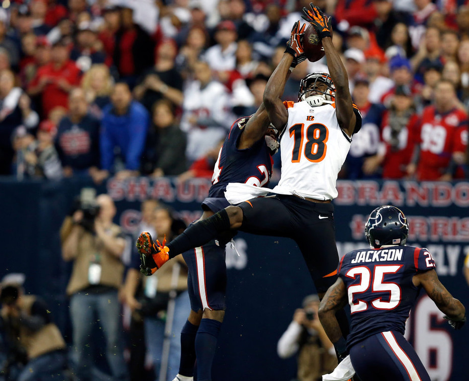 Description of . A.J. Green #18 of the Cincinnati Bengals can't make a catch against Johnathan Joseph #24 and Kareem Jackson #25 of the Houston Texans during their AFC Wild Card Playoff Game at Reliant Stadium on January 5, 2013 in Houston, Texas.  (Photo by Scott Halleran/Getty Images)