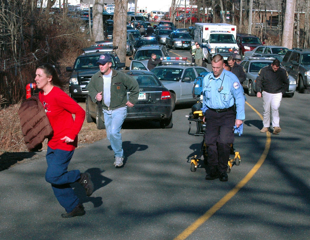 Description of . In this photo provided by the Newtown Bee, paramedics and others rush toward Sandy Hook Elementary School in Newtown, Conn., where authorities say a gunman opened fire, killing 26 people, including 20 children, Friday, Dec. 14, 2012. (AP Photo/Newtown Bee, Shannon Hicks)