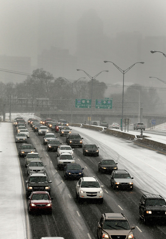 Description of . Drivers pack the roads as they leave downtown Charlotte, N.C., Wednesday, Feb. 12, 2014, as a winter storm moves into the area. (AP Photo/Chuck Burton)